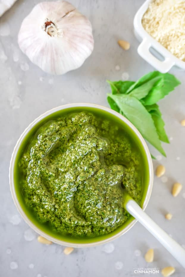 Bright green basil pesto in a small bowl with a white spoon, some basil leaves, a few pine nuts, a garlic clove and grated parmesan cheese.