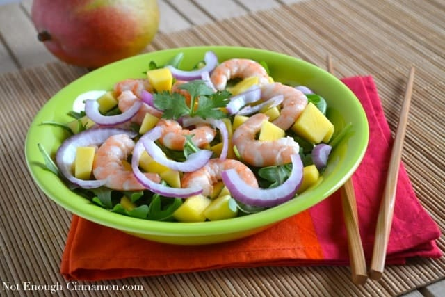Mango Shrimp Arugula Salad topped with red onion slices and cilantro, served on a green plate placed on a bamboo mat with a mango in the background