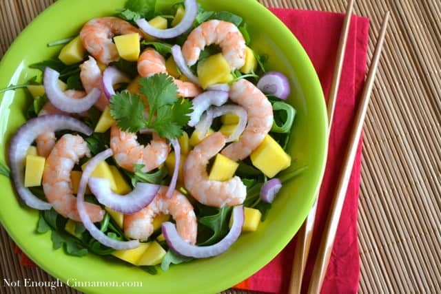Overhead shot of Mango Shrimp Arugula Salad served on a green plate placed on a bamboo mat with chopsticks on the side