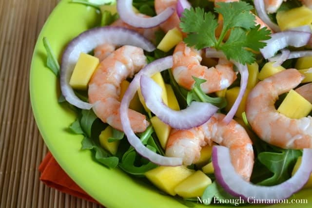 Close-up of Mango Shrimp Arugula Salad topped with red onion slices and fresh cilantro