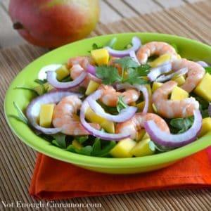 Mango Shrimp Arugula Salad served on a green plate
