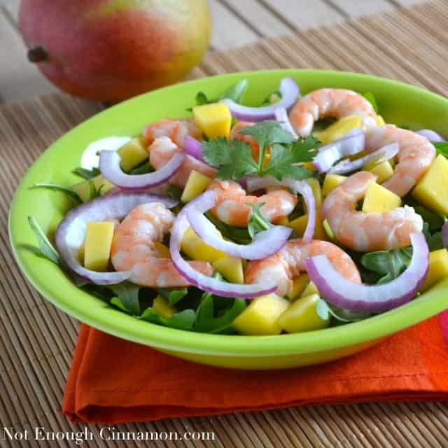 Mango Shrimp Arugula Salad served in a green bowl