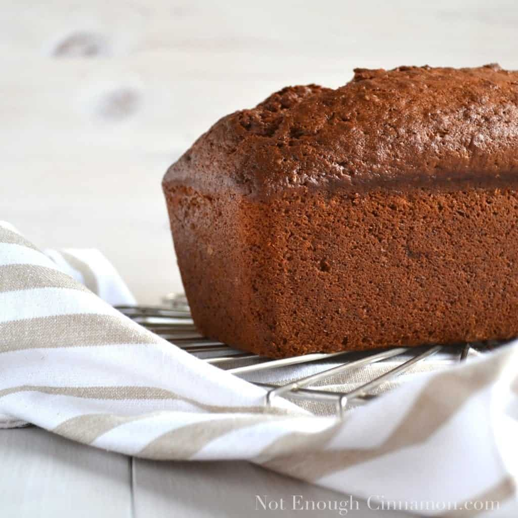 side view of a loaf of banana bread cooling on a rack