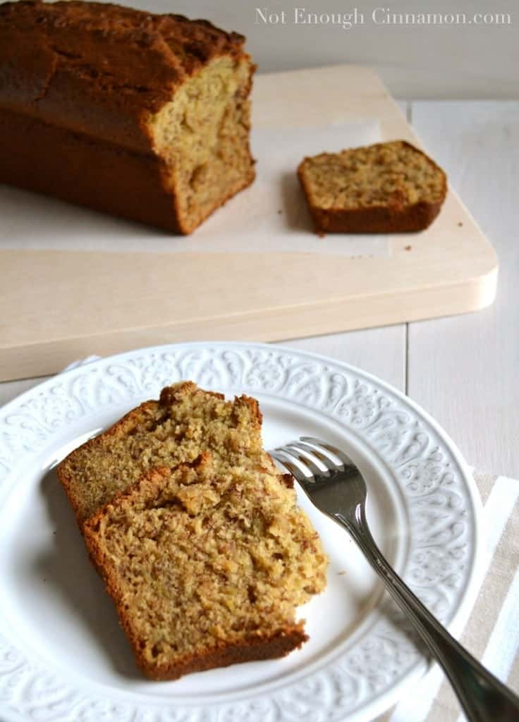 two slices of moist banana bread on a white plate with a loaf of best banana bread in the background