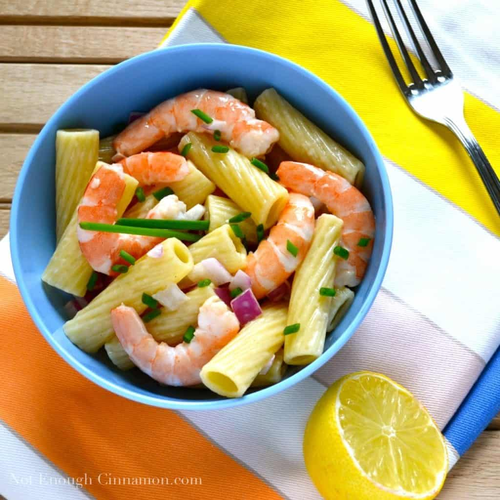 penne rigate pasta salad with fresh cooked shrimp and chopped chives served in a blue bowl on a striped napkin