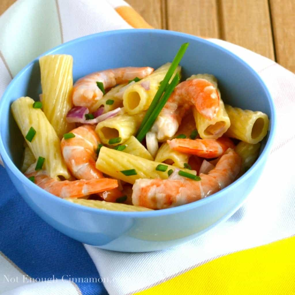 side view of rigatoni pasta salad with cooked shrimps, chopped red onions and chives in a light mayo dressing served in a blue bowl on a colorful napkin