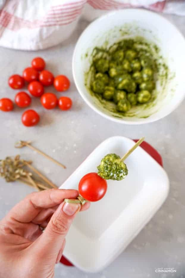 Hand holding a tomato, pesto and mozzarella skewer being made, with cherry tomatoes, pesto covered mozzarella balls and wooden skewers in the background.