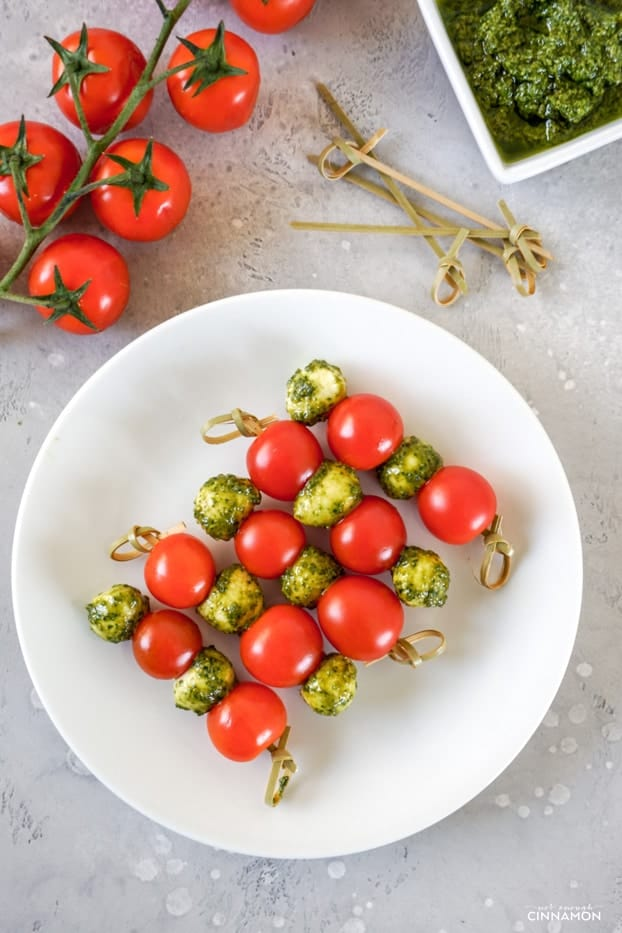 Five tomato, pesto and mozzarella skewers on a white plate, with pesto, grape tomatoes and wooden skewers in the background.