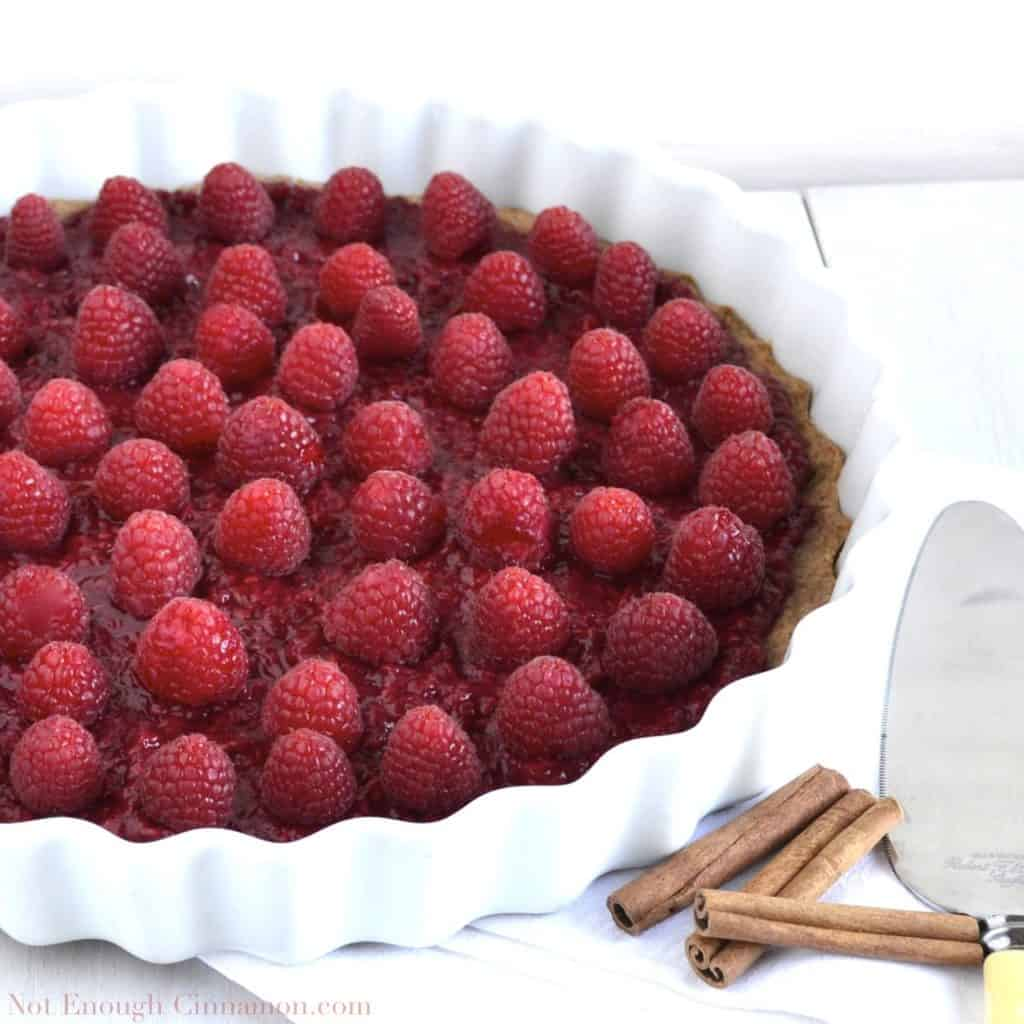 Skinny Raspberry Tart on whole wheat cinnamon crust in a white tart dish with some cinnamon sticks on the side
