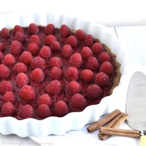 Raspberry Tart with Cinnamon Crust in a white tart dish with some cinnamon sticks on the side