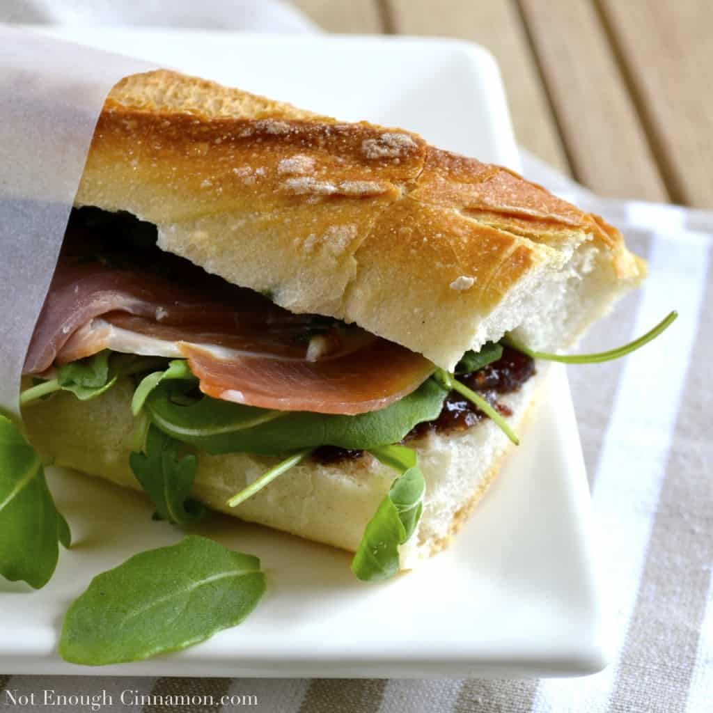 side view of a prosciutto sandwich with pesto, arugula and fig chutney served on a white plate with a strip of sandwich paper holding it together