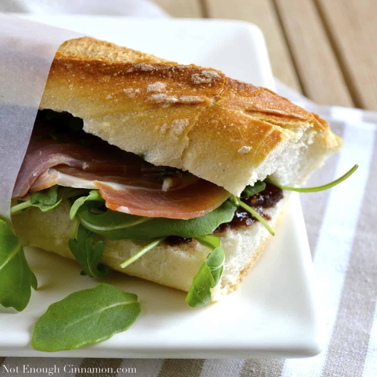 Prosciutto Sandwich with Pesto, Arugula and Fig Chutney wrapped in sandwich paper and served on a white plate