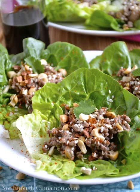Asian Lettuce Wraps with Beef Filling sprinkled with sesame seeds and peanuts and arranged on a white plate