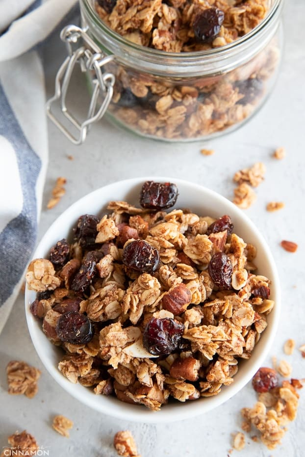 Granola is a small bowl with a white and blue stripped kitchen towel