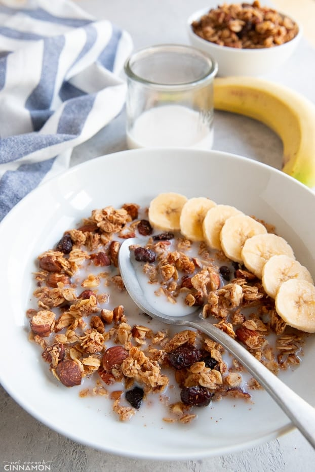 Granola is a white bowl with milk and sliced banana, with a silver spoon