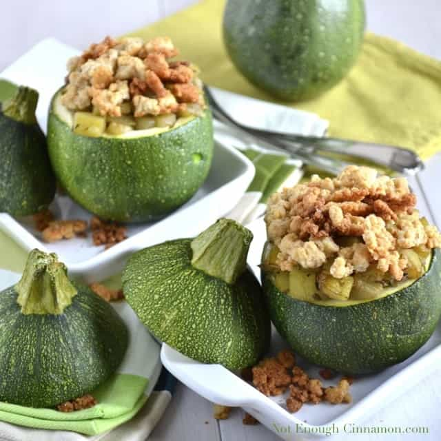 Stuffed baked 8 Ball Zucchini with Parmesan Crumble served on 2 white plates with some crumble on the side and the cut off zucchini lids next to the plates