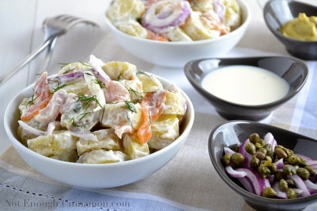 Smoked Salmon Potato Salad with a creamy dill dressing and topped with fresh dill served in 2 white bowls with a small dish with capers and red onion slices on the side