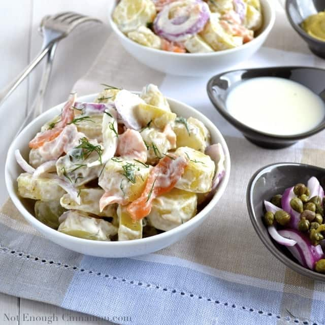 Smoked Salmon Potato Salad with a creamy dill dressing and topped with fresh dill served in 2 white bowls with 2 small back dishes with dressing and capers on the side