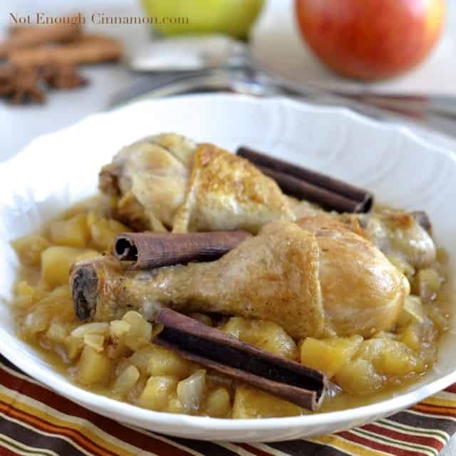 Chicken Stew with apples and cinnamon served in a white bowl with some cinnamon bark and apples in the background