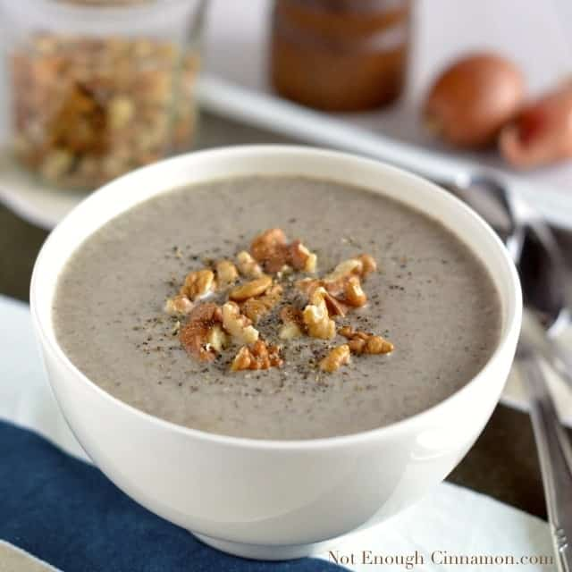 Skinny Cream of Mushroom Soup served in a white bowl with some chopped walnuts and freshly grated pepper on top