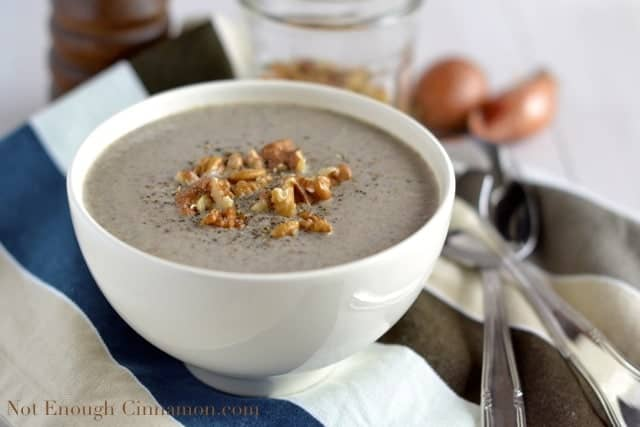 a white bowl of Skinny Cream of Mushroom Soup topped with chopped walnuts and freshly grated pepper