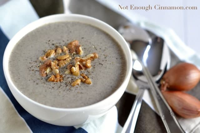 a white bowl of Skinny Cream of Mushroom Soup topped with chopped walnuts and freshly grated pepper with spoons and shallots on the side