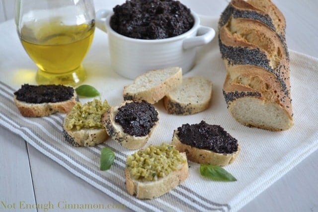 Green and Black Olive Tapenade spread on poppy seed baguette slices with a dish full of tapenade and a bottle of olive oil in the background