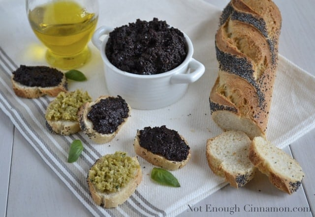 Green and Black Olive Tapenade spread on poppy seed baguette slices with a dish full of tapenade in the background