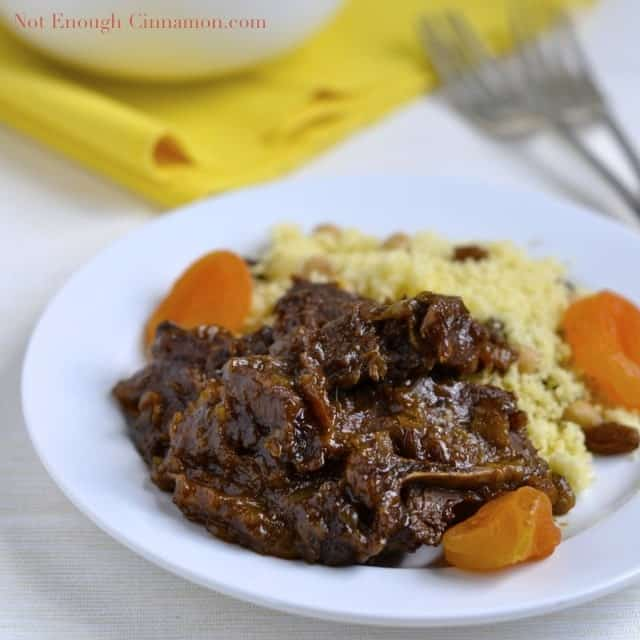 Delicious Lamb Tagine with dried Apricots served with a side of raisin studded couscous on a white plate