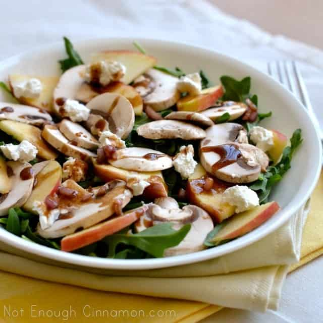 Mushroom, Apple and Goat Cheese Salad with Honey-Balsamic Dressing served on a white plate with a fork on the side