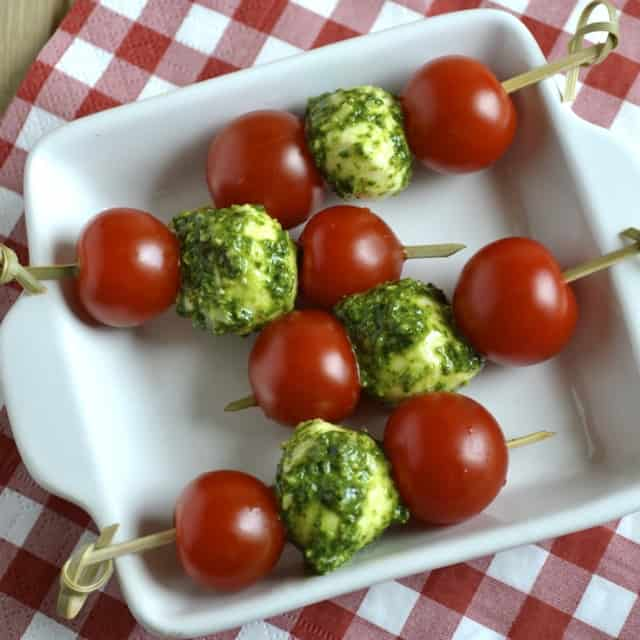 Tomato, Pesto and Mozzarella Skewers served on a white plate