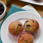 overhead shot of Blueberry-Banana Bread Muffins served on a white plate with a muffin tray and fresh blueberries in the background