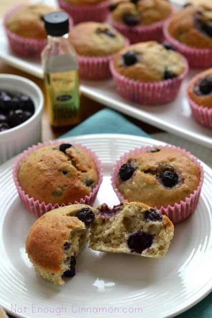 Blueberry Banana Bread Muffins served on a white plate with the front muffin being torn into halves to reveal the moist, fluffy centre.