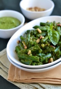 Crispy Green Beans with Pesto served in a white oval dish with some fresh basil and pine nuts sprinkled on top