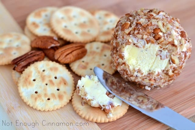 a small portion of Pecan Cheese Ball being spread on a Ritz Cracker with a butter knife