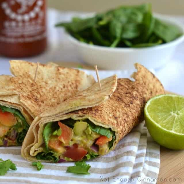 side view of 2 shrimp Avocado Wraps placed on a kitchen towel with a side salad in the background