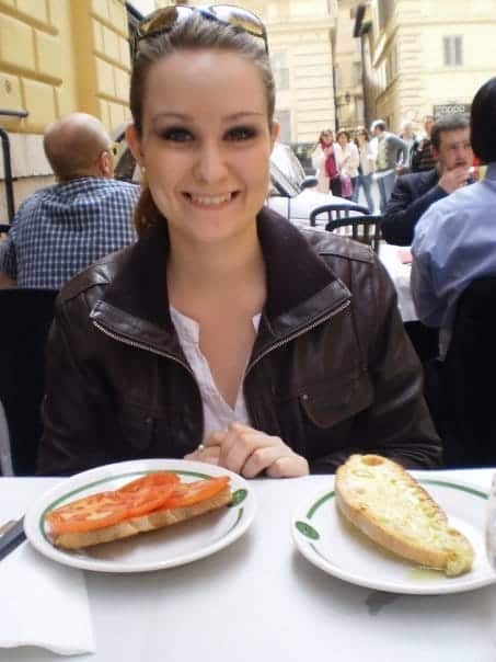 a woman sitting enjoying her bruschetta at an outside eatery in Rome