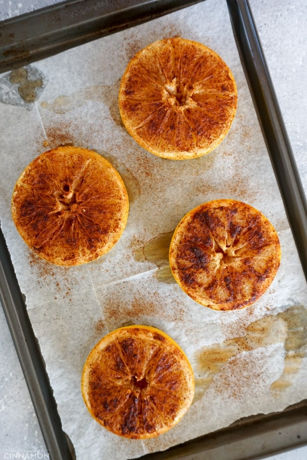 Four baked half grapefruits on a line baking sheet.