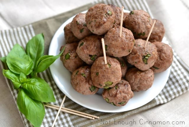 Basil Ricotta Meatballs piled up on a white plate with some toothpicks inserted into them