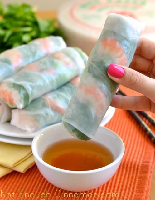Vietnamese Spring Rolls being dipped into a small dish with dipping sauce with a plate full of spring rolls in the background