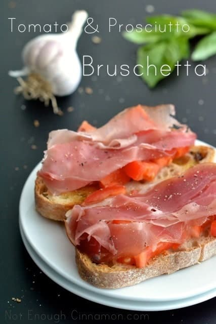 2 pieces of Prosciutto Tomato Bruschetta on a white plate on a black tabletop with garlic and basil in the background