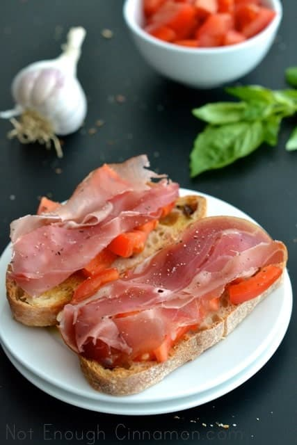 2 pieces of Prosciutto Tomato Bruschetta on a white plate placed on a black tabletop with garlic and basil in the background