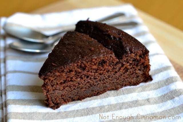 a slice of Chocolate Yogurt Cake on a striped napkin with 2 spoons in the background