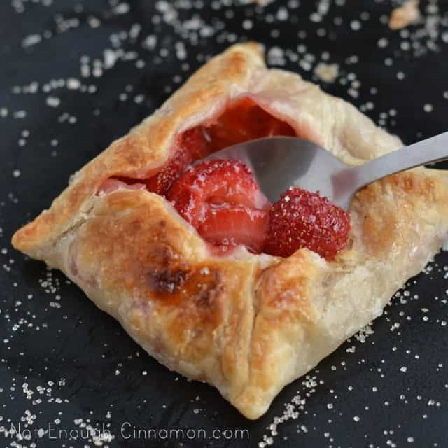 a silver spoon being dipped into the still warm center of a freshly baked strawberry mini pie