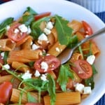 Pasta Risotto in a white bowl sprinkled with feta cheese, tomatoes and fresh arugula