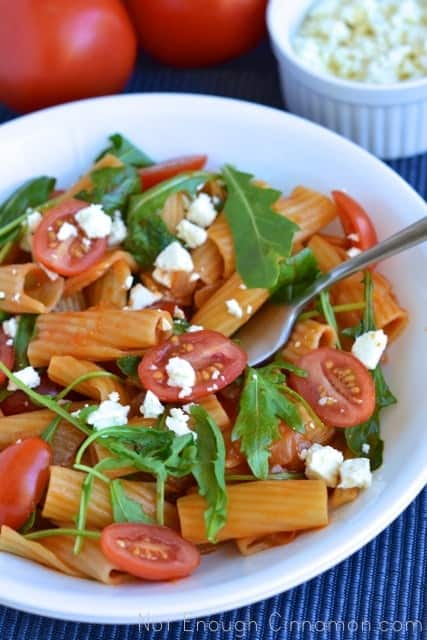 Pasta Risotto served in a white bowl with arugula, cherry tomatoes and some crumbled feta cheese