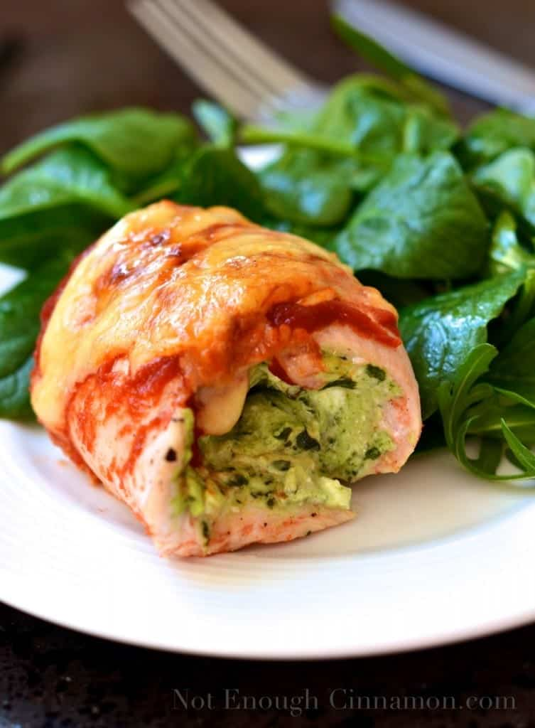pesto and cream cheese stuffed chicken rollatini on a white plate
