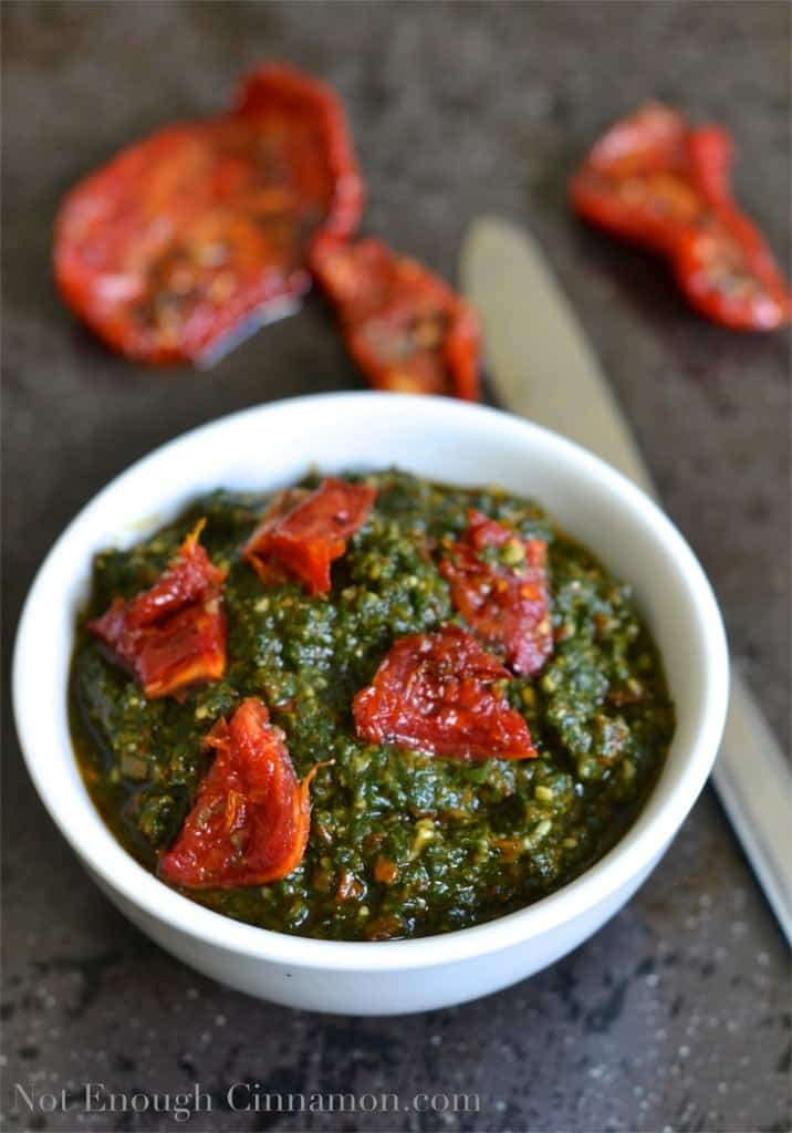 Basil and Sun-dried Tomatoes Pesto in a small white bowl with some sun-dried tomatoes in the background