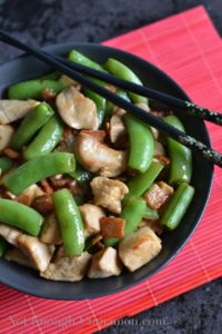 Bacon, Chicken and Snow Peas Stir-Fry served in a black bowl with some chopsticks on the side