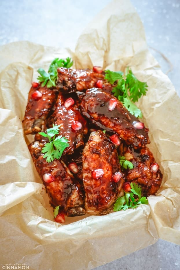 Baked chicken wings with pomegranate glaze in a container with brown paper